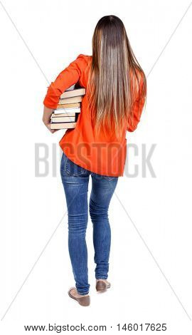 Girl comes with stack of books. back side view. student in red jacket goes back frame difficult holding a stack of books.