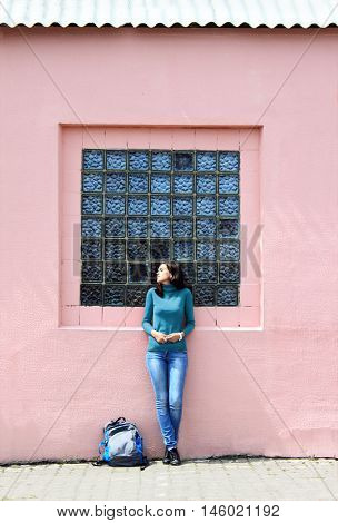 Girl in a saturated aqua sweater in pale pink walls.  Portrait in full growth