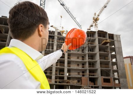 Portrait of young construction engineer pointing at building under construction with red hardhat