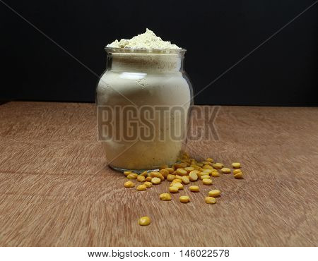Chickpea flour in a bottle, and lentils, on a wooden background.