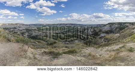 A scenic panoramic of a badlands river valley.