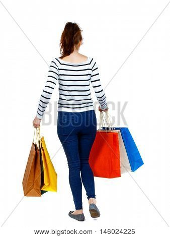 back view of going woman with shopping bags . beautiful girl in motion. Girl in a striped sweater went off with colorful bags.