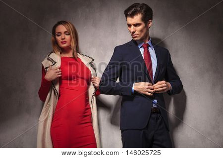 business man buttoning his suit and looks back at his sexy blonde girlfriend wearing red dress and log coat
