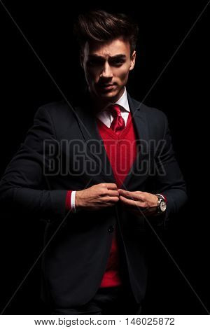 serious young business man unbuttoning his suit  on black background in studio