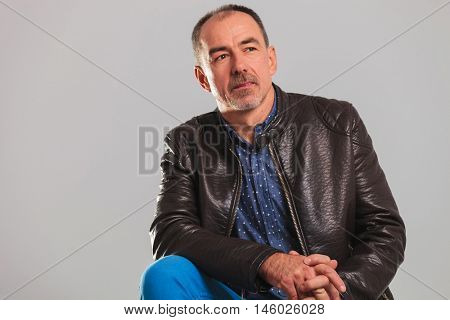 side view of a seated mature casual man in leather jacket , looking away fron the camera