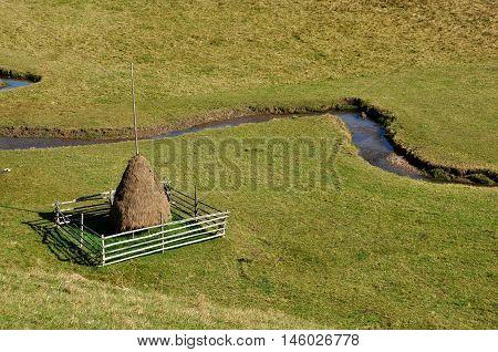 Haystack in a green meadow. Small watercourse near
