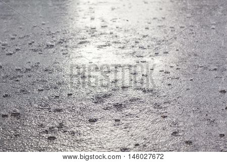 Rain on the asphalt. Cold october. Water surface with a lot of drops.