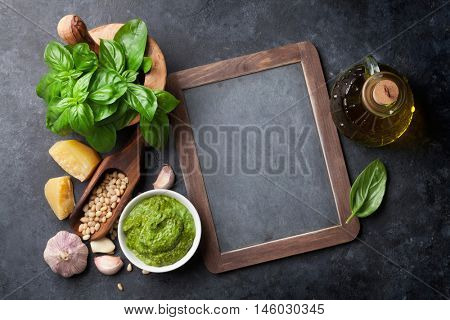 Pesto sauce cooking. Basil, olive oil, parmesan, garlic, pine nuts. Top view with chalkboard for your text