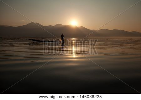Intha fisherman fishing at sunset in his typical canoe with fishing net