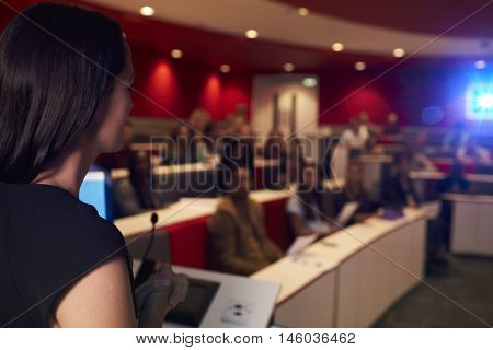 Woman lecturing students in lecture theatre, focus foreground
