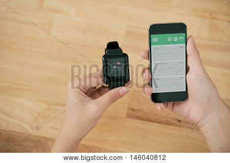 Hands holding smart watch and smartphone with healhcare app