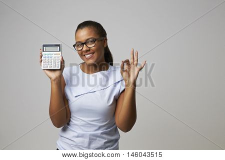 Studio Portrait Of Female Accountant Using Calculator