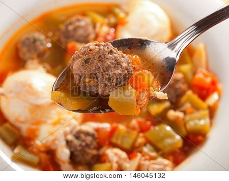 Tunisian soup with meatballs and eggs. Detail on spoon with meatball