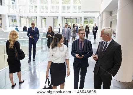 Businesspeople In Busy Lobby Area Of Modern Office poster