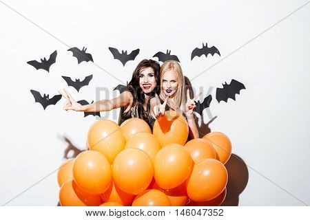 Two smiling beautiful women with vampire makeup and orange balloons having fun over white background