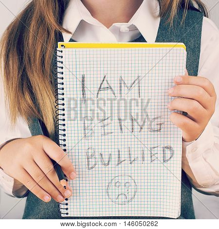 An image covering the Social Issues of child abuse schoolchild in uniform asking for help by a written message saying I am being bullied with a sad face . square format with an added instagram style filter