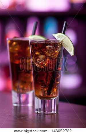 Cuba Libre is a famous Cuban cocktail. It is made of 2 oz light rumjuice of 1/2 limesCoca-Cola. Shot on a bar in purple light