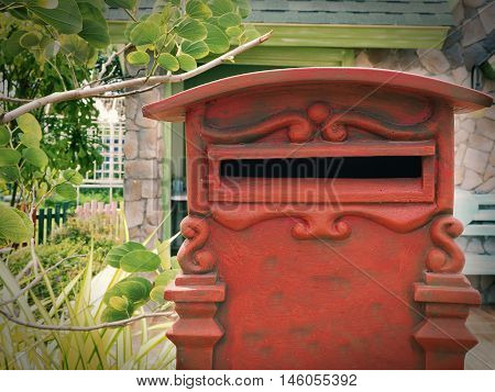 Old red mailbox with garden background.Retro mailbox style.