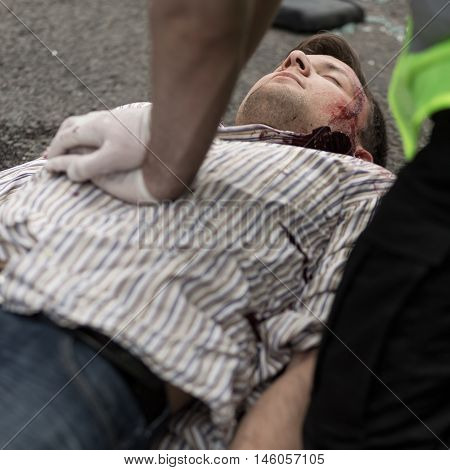 Policeman doing chest compression to injured man
