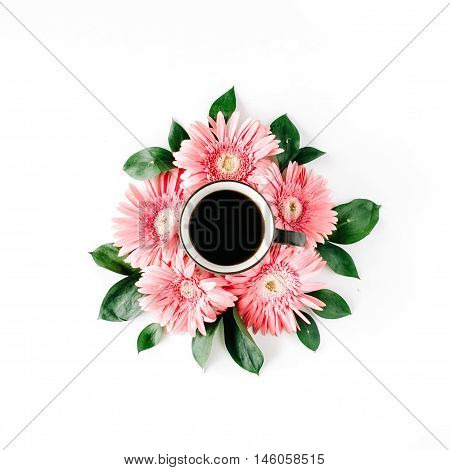 black coffee mug and pink gerbera flowers bouquet on white background. flat lay top view