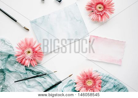 Workspace. Pink gerbera buds and watercolor paper with paintbrush and blue textile on white background. Flat lay top view
