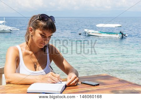 yung pretty woman freelancer writer working with notepad and phone infront of blue tropical sea at sunny day under blue sky
