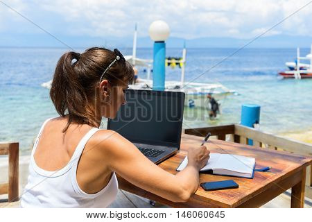 yung pretty woman freelancer writer working with laptop notepad and phone infront of blue tropical sea at sunny day under blue sky