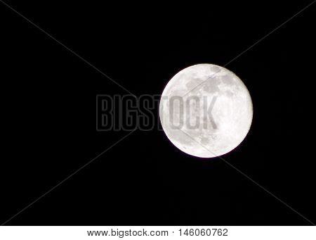 Full moon against dark black sky showing terrain on the moon.