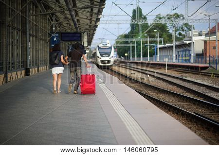 The young pair costs on platform having joined hands. The young man rolls a red suitcase. Both hasten on a train which comes close.