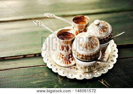 Two cups of bosnian traditional coffee on a wooden table