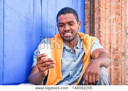 Cheerful afro american man texting sms sitting next to blue wooden door - Handsome black guy using mobile phone relaxing backed to wall outdoors in town - Concept of internet modern communication