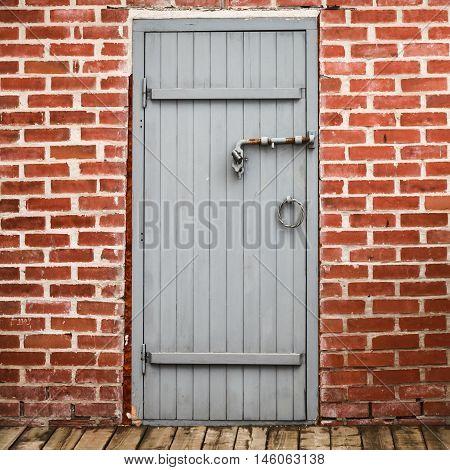 Gray Wooden Door In Old Red Brick Wall