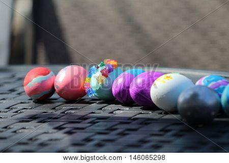 Eight colored easter eggs on iron, gridded table.