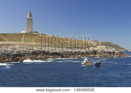 Spain Galicia A Coruna Hercules Tower Lighthouse in daylight clear sky Atlantic Ocean waters a boat