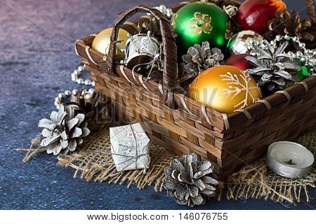 Preparation for Christmas. Basket with ornaments for a Christmas tree, candle and pine cones on a blue background.