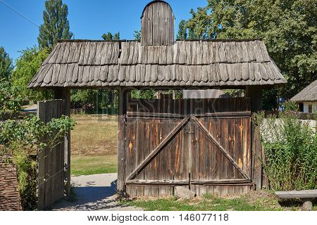 Old wooden gate with a wooden roof built in the mid-eighteenth century. View from behind