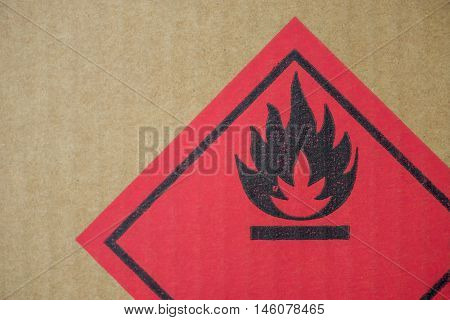 Close-up detail of a fire hazard warning symbol on a cardboard cargo box containing chemicals.