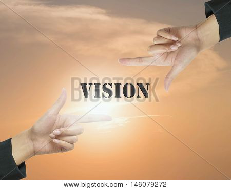 Closeup vision word at the center frame by hand of working woman on beautiful evening sky textured background in work concept