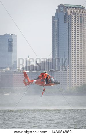 JERSEY CITY NJ MAY 29 2016: U.S. Coast Guard rescue swimmer jumps into the Hudson River from a USCG MH-65 Dolphin helicopter hovering above during a Search and Rescue demonstration, Fleet Week 2016.