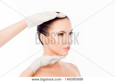 Doctor In Medical Gloves Examining Woman's Face After Surgery