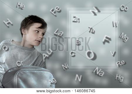 Children and formulas. cute girl with school backpack on the background of table of Mendeleev