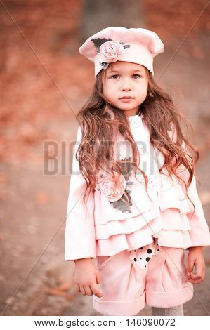 Stylish kid girl 3-4 year old wearing winter jacket shorts and hat outdoors. Looking at camera. Childhood.