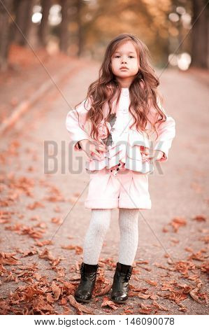 Stylish baby girl 4-5 year old wearing winter jacket and shorts standing outdoors. Looking at camera. Autumn time.
