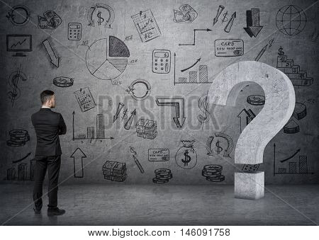 Back view of businessman touching big 3D concrete question mark on the backgound with business doodles. Economy and finance. Money and profit. Successful lifestyle.