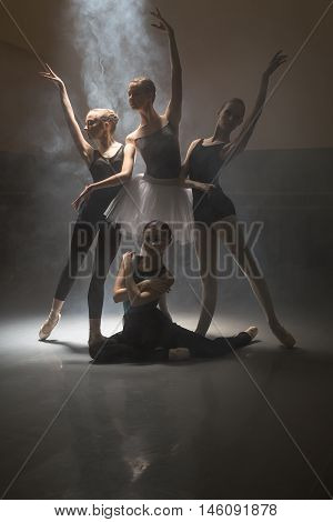 Four young ballet dancers posing in the dark dance hall. One of them sitting on the floor while others stand. Light falls down from above. Low key photo.
