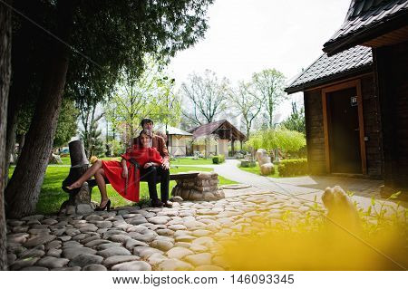 Couple Sitting On Bench. Stylish Man At Velvet Jacket And Girl In Red Dress In Love Together