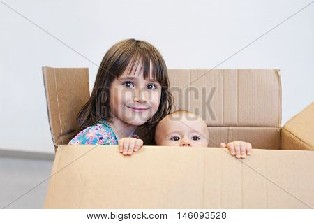 Happy sisters playing in a carton box