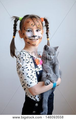 Sweet portrait of a cute little girl with face painted like a leopard holding a gray kitten
