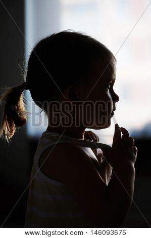 Silhouette of todler girl alone in the front of a window