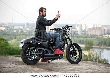 Stylish man with a beard sits on the black motorbike near the cliff on the background of the river and the city. He holds the red cellphone in his hands in front of himself. He wears a blue ripped jeans, red sneakers and a black leather jacket.